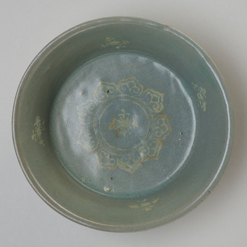 bowl shallow, underglazed in white with floral medallion, and four sprays on sides; celadon