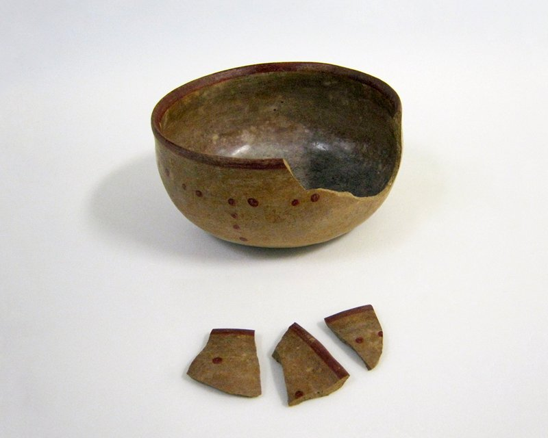 bowl, with red slip dot and circle pattern. also rim band; traces of grey slip interlacing band and circle design on outside of bottom; burnished buff clay; Chinesco? Three pieces broken from side of bowl in area 3-3/4 x 1-3/4 in.