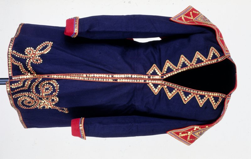 man's coat; navy blue with red lining, red braid trim and gold metal sequin and glass bead decoration; red cape-like sequinned collar; 4 tassels at sides (stored in box)