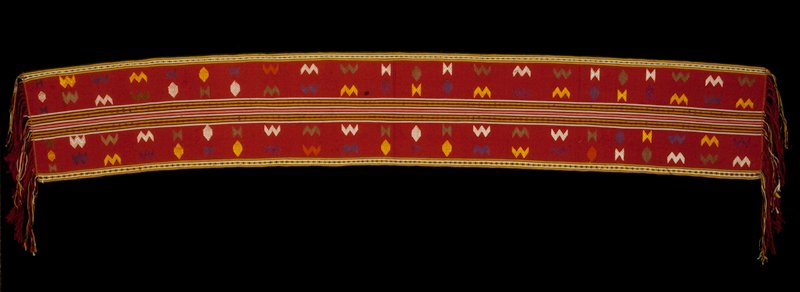 Chaksay Pankhep, royal/relgious lap cover; silk/ cotton brocade on cotton background; red with multicolored stripes at center; discontinuous supplementary weft pattern; supplementary warp along borders; fringe.