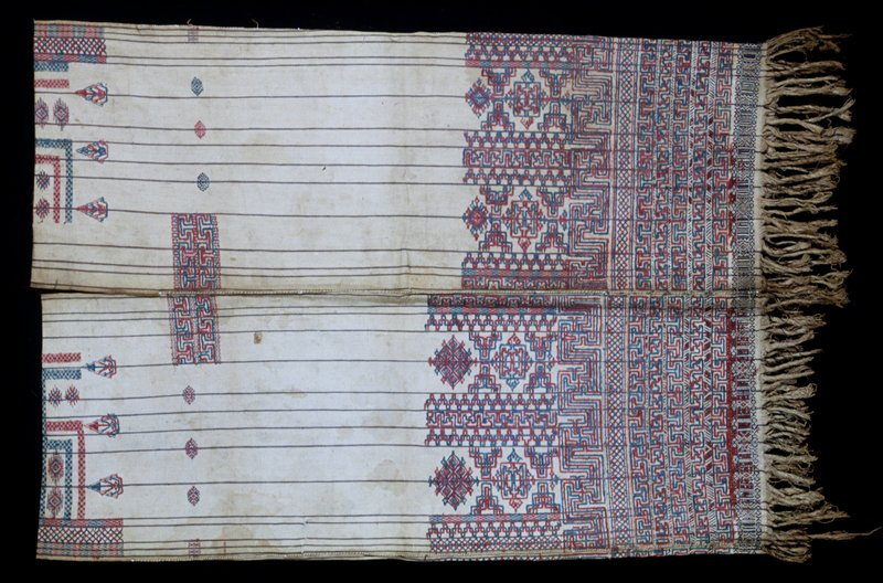 Tunic, silk design on cotton ground; 2 panels sewn together; neck and armsholes; fringe; discontinuous supplementary weft pattern in red and blue on naturl ground with thin red and blue stripes