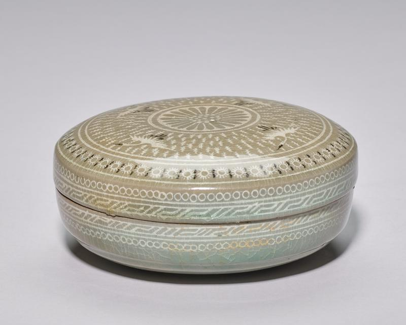 covered round box with chrysanthemum medallion in center surrounded by four cranes; grey celadon glaze with black and white slip