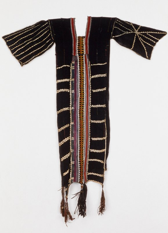 garment, cotton,stripwoven, embroidered, applique border, three pairs of leather tassels at each end; tassels have button, beads, cowrie shell decorations, African (Niger-Fulani) stored in box,(Simmons); stored w/86.100.22,.30,.33,.34