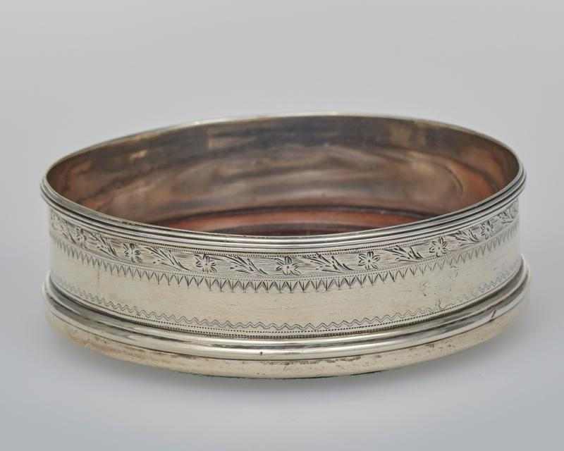 circular wine coaster with turned wood base, reeded lip; sides engraved with wriggle work bands and floral entwined reeding; fully marked on lower edge of exterior; one with obscured maker's mark