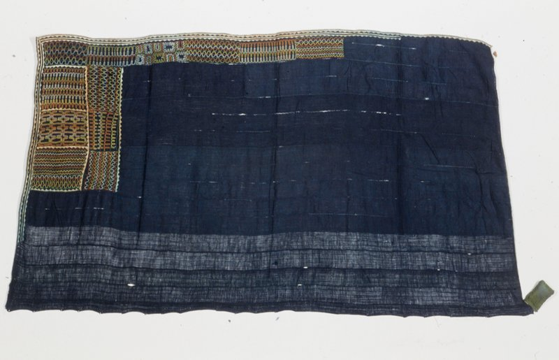 skirt, indigo dyed strip cloth with embroidered and appliqued trim; spice packet attached; cotton