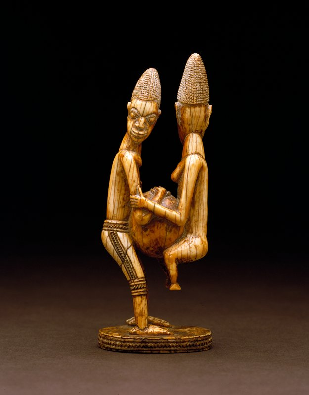 man and woman with a calabash; Yoruba Tribe; pair of figures carved in ivory; the male figure is standing and holding a round vessel, his hands at its opening; the female clings to his arms, over the vessel, her feet off the ground