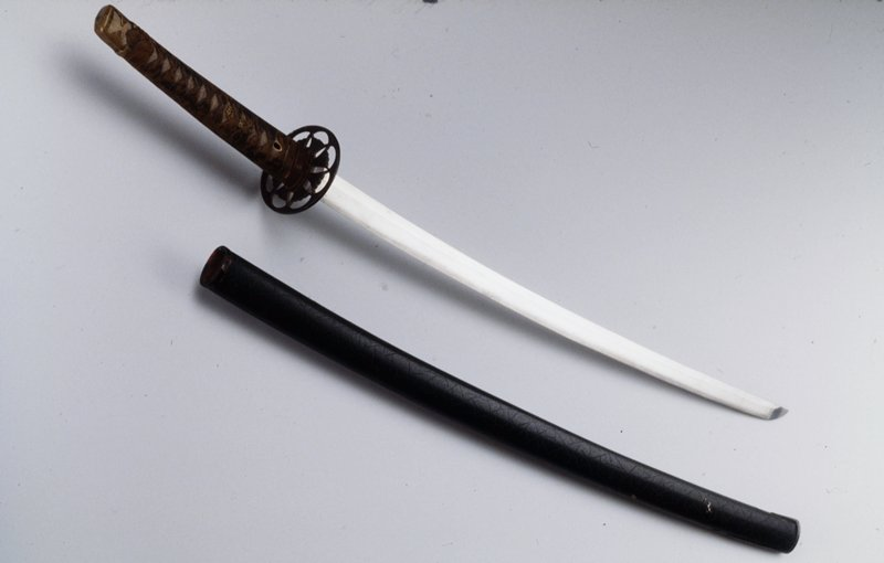 long sword with scabbard: a. scabbard-lacquered wood b. handle-wood, sharkskin and silk cord c. shortened blade with 2 peg holes and iron tsuba d. Hilt (Tsuka) e. pommel (fuchi) f. spacer (seppa) g. spacer (seppa)