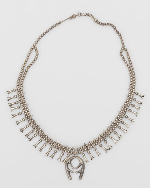Double strand of small silver beads with 29 4-pronged sq. bloss., cast silver naja, silver charm, silver clasp. J.#455, Cat.#397.