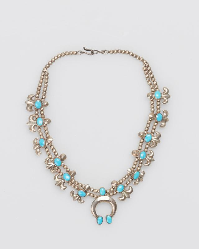 """Child's necklace; Double strand of tiny silver beads; twelve cast """"cornflowers"""" on shanks; set with elliptical turquoises; cast naja set with three elliptical Lone Mountain turquoises at apex and terminals J.#476, Cat.#471."""