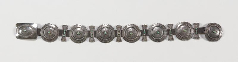 Navajo leather belt with rectangular buckle; six round conchas and six modified 'butterfly' plaques, each set with a round turquoise; chased and applique decoration. J# 1083, Cat# 570, Illustraated p 138. There is an additional loose concha which matches the belt, tagged L77.66.1083