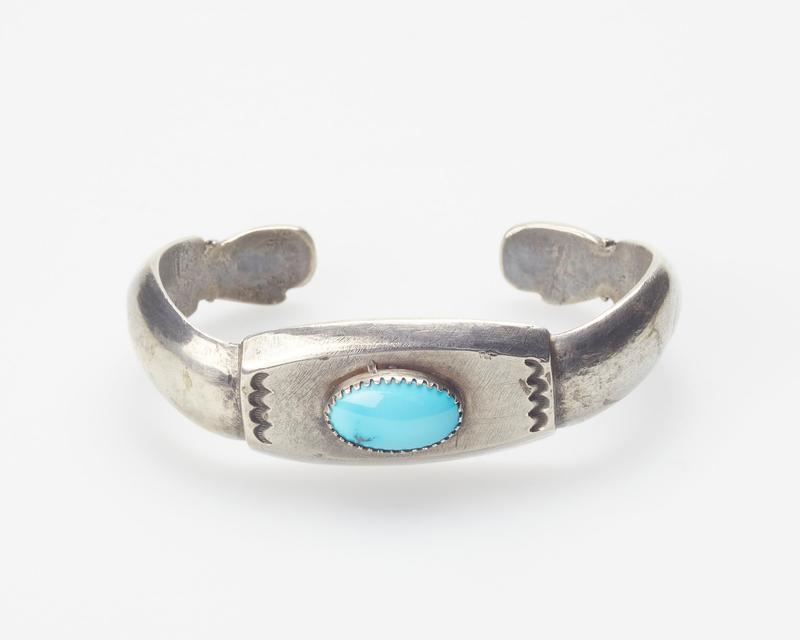 Cast band terminating in hands, set with single elliptical Burnham turquoise in serrated bezel; stamped decoration cat. 321, J#67