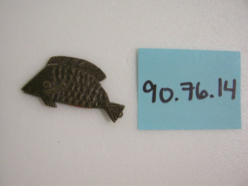 Flat fish with small triangular tail and incised detail.