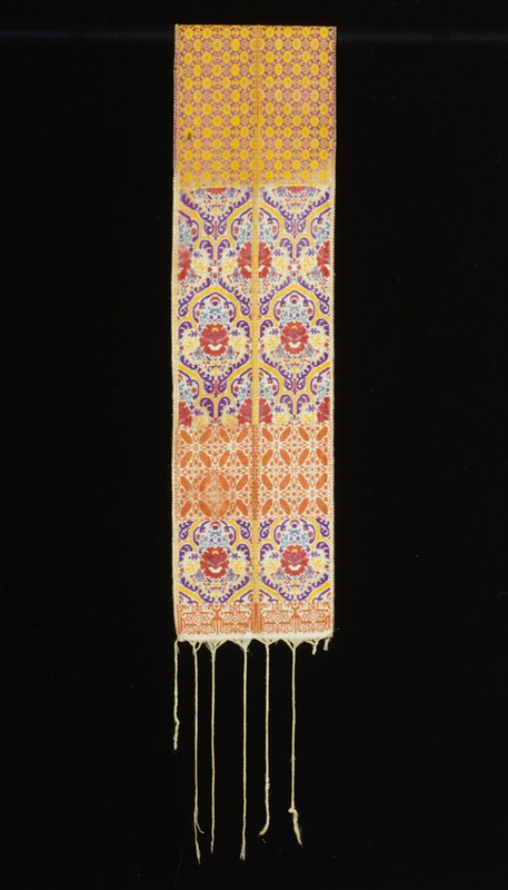 half gold geometric patterning on purple ground and half purple, red and yellow floral patterning on white ground, with band of orange on white geometric patterning near end