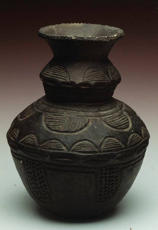 Earthenware vase with incised half circle line designs along the top half of vase, bottom half has rectangular sections of raised dots.