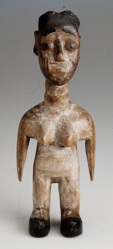 Wooden female figure with long neck; white patina throughout; black hair, facial features, and shoes