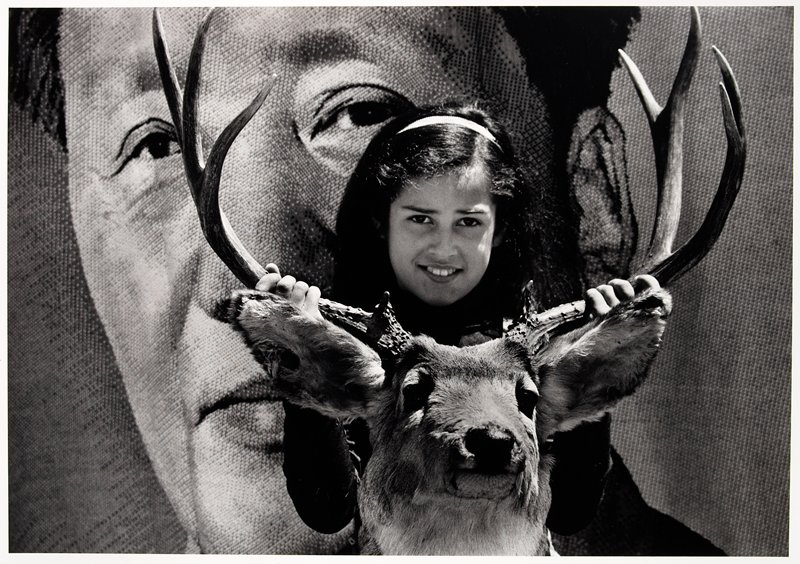 young girl holding a stuffed buck's head by the horns