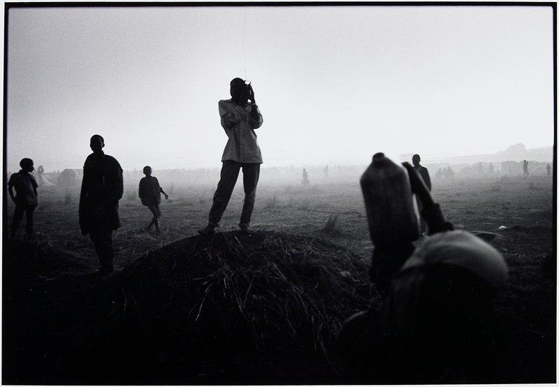 man standing on mound holding radio