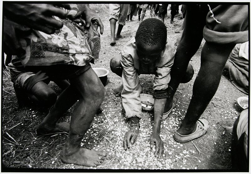 boy scooping food off the ground with his hands