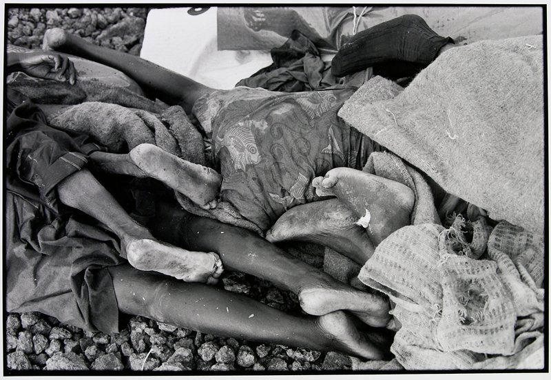 feet and legs of dead bodies; one person's lower back, covered with a fish-print fabric, dominates the center of the image