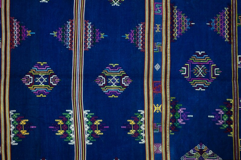 three panels joined; fringe on both ends; silk brocade with supplementary weft patterning; blue field with bands of geometric design; side stripes red, blue, green and yellow