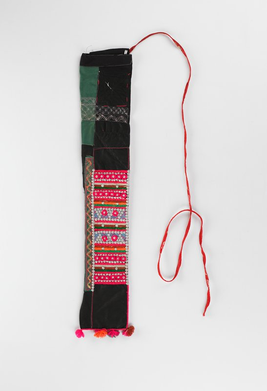 long rectangular folded and sewn in one corner with pom-poms along top edge; one long red tie string on opposite end; multicolored embroidery throughout with metal decorations on one side