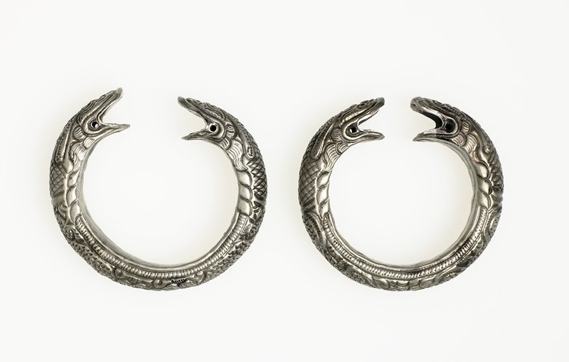 open bracelet; design of two dragons back to back with mouths open, facing each other at opening of bracelet; hollowed out inside with beads inside which make noise when bracelet is moved