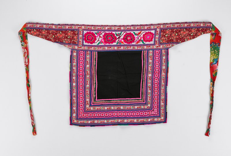 waistband decorated with large unfinished band of embroidery showing four large flowers; main body of apron is made of black and is decorated with four bands of embroidery and ribbon is forming a squared 'U' shape