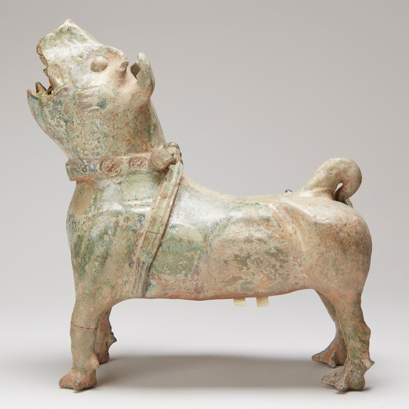 green glaze; barking, standing looking forward, ears pricked; medallion-impressed collar and thick plain strap round front of bells; small loop tail and short legs with claw feet; dark apple glaze extensively crackled and degraded to a rich silvery-green iridescence