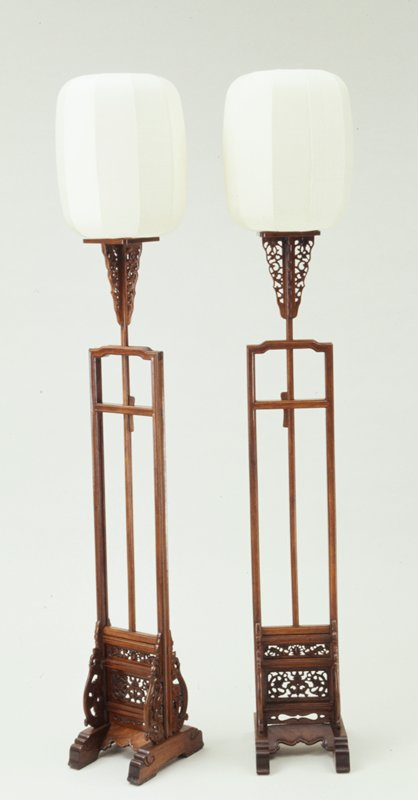 square candle stand supported by four open work spandrels above a central adjusting post; two small openwork panels at base