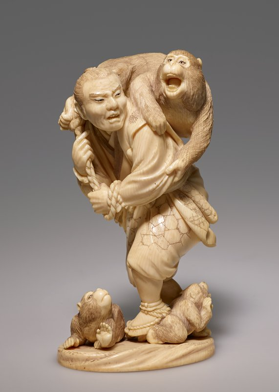 carved figure of a hunter carrying a large monkey on his back with two smaller monkeys at his feet