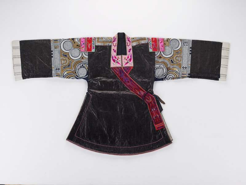 brown and white batik, upper sleeve, top of shoulder and half circle at upper center back; embroidered shoulder, neck, opening trim and two wedges on back tails; shiny black body and lower sleeve with white cuffs