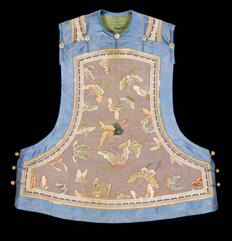 grey with scattered butterflies, 1-1/2 in. of blue trim around all sides; grey buttons near shoulders; brass buttons on both sides