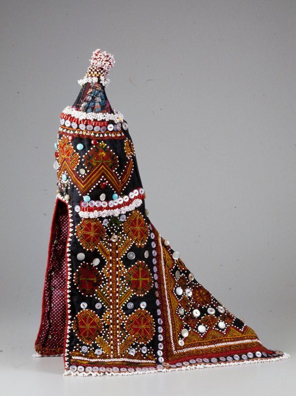 cap with extended shoulder cover; black ground, silk embroidery in red, gold, green and purple of geometric diamond patterns; small white beads highlight designs; buttons at borders of area divisions and interspursed with design