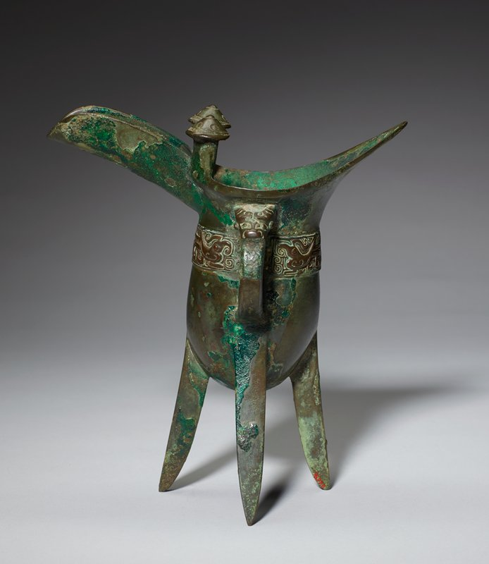 tripod vessel with handle and elongated spout; decorative band around middle