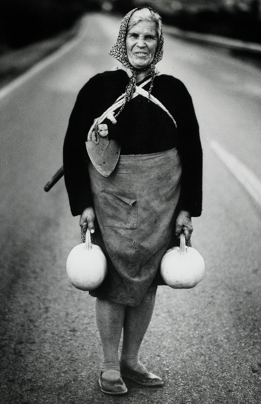 black and white; woman in road with a squash in each hand