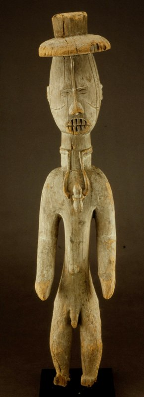 Standing Male Figure with Hat, wood, African (Nigerian, Ijo), XXc on base cat. card dims H 32' Figure wears European hat, medicine gourd suspended from neck; feet are missing.