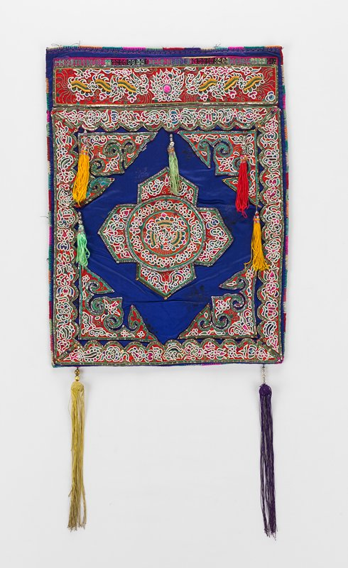 purple field with embroidered applique; five tassels hang within field; two larger tassels, green and purple hand from bottom edge; black backing