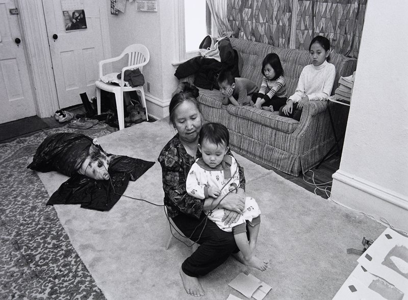 black and white photo of old woman holding child, pig wrapped in plastic of floor behind, while three children on couch look on