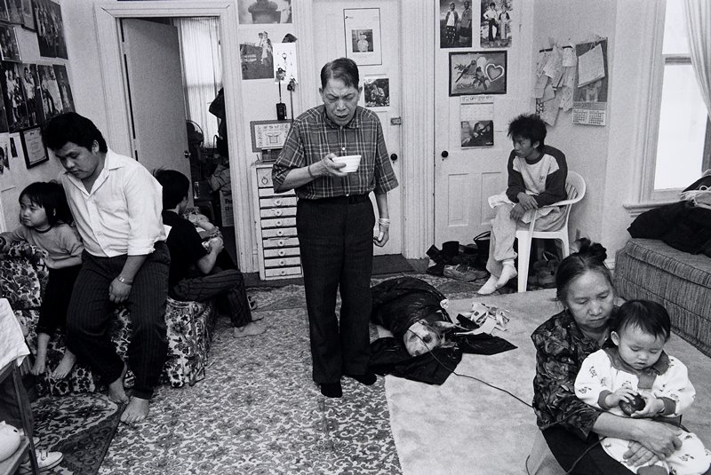 black and white photo of man in center of room holding bowl; pig on floor in plastic bag; people seated around room