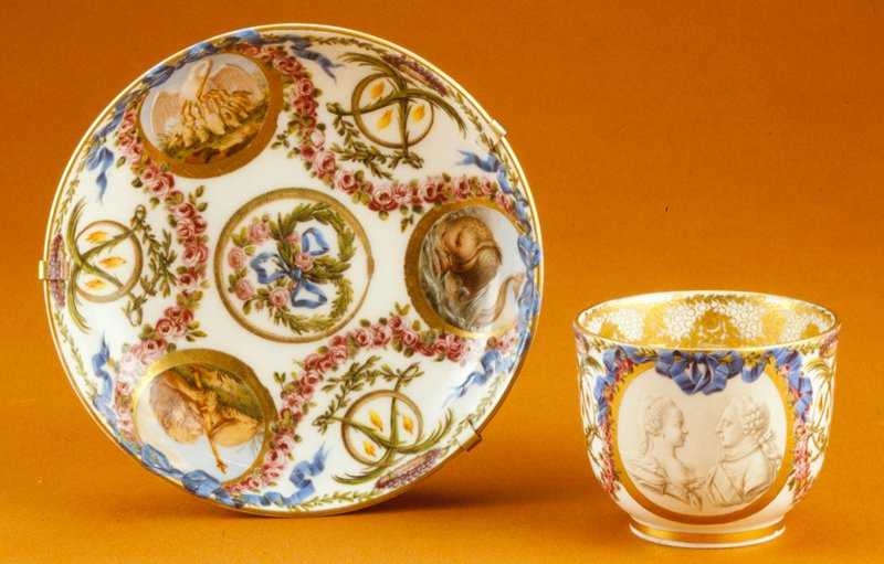 saucer, cermaic-porcelain, cup and saucer from a dejeuner, painted with portraits of Louis XVI and Marie Antoinette; the crossed L's in the foliage refer to Louis, and much of the iconography (rings, birds, etc.) refer to a marriage or betrothal