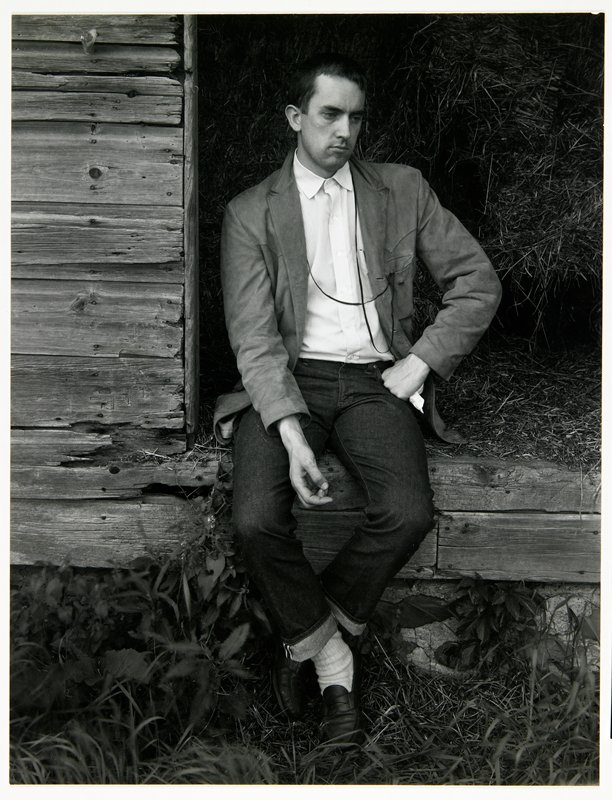man in blue jeans, penny loafers and a jacket sitting in front of an open doorway with hay visible behind him; mounted on board