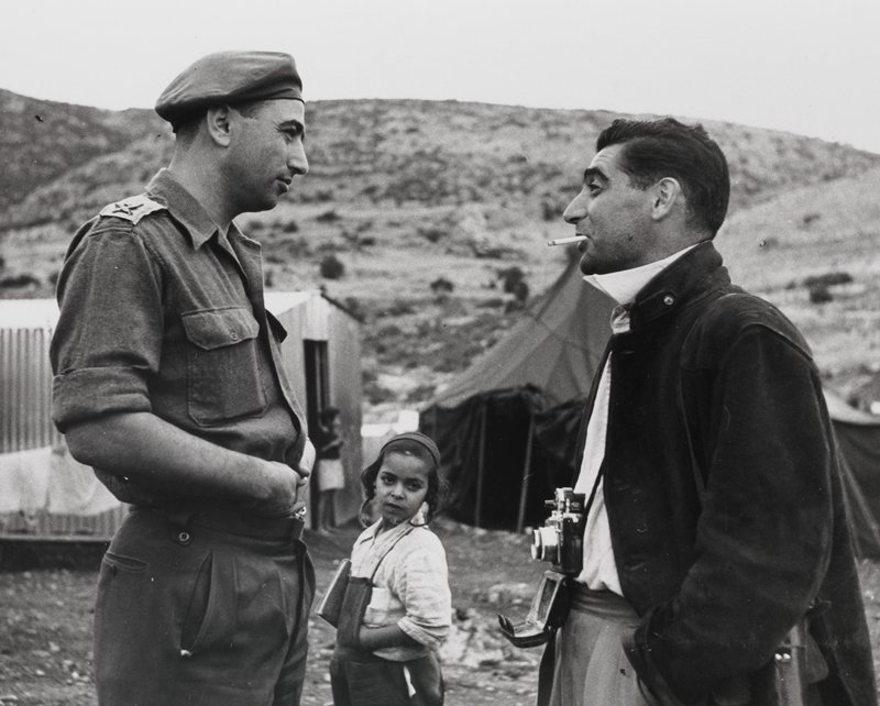 man at left, in profile, wearing a uniform and beret facing a man at right, in profile, wearing a jacket and a camera around his neck, with a cigarette in his mouth; Jewish boy in background between men; framed