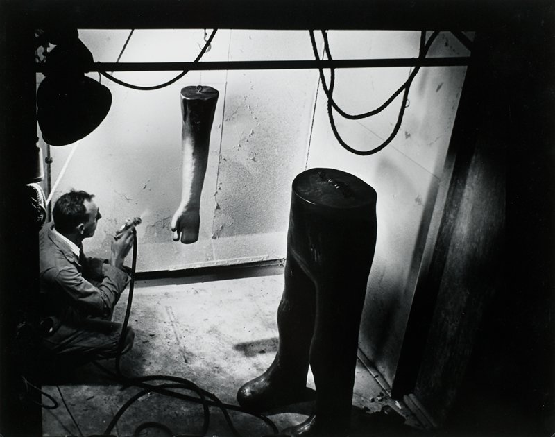 Kneeling man spray painting a mannequin's arm; mannequin legs in foreground