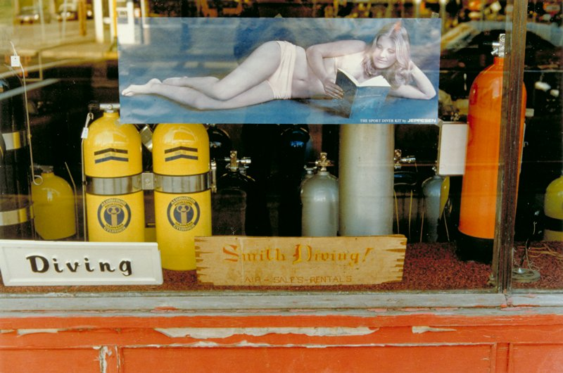 storefront window with poster of woman in swimming suit reading a book