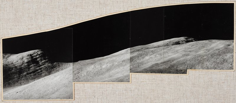four separate photographs mounted together for a panoramic view of barren landscape, black sky and bluff at left; mounted on a cloth-covered board