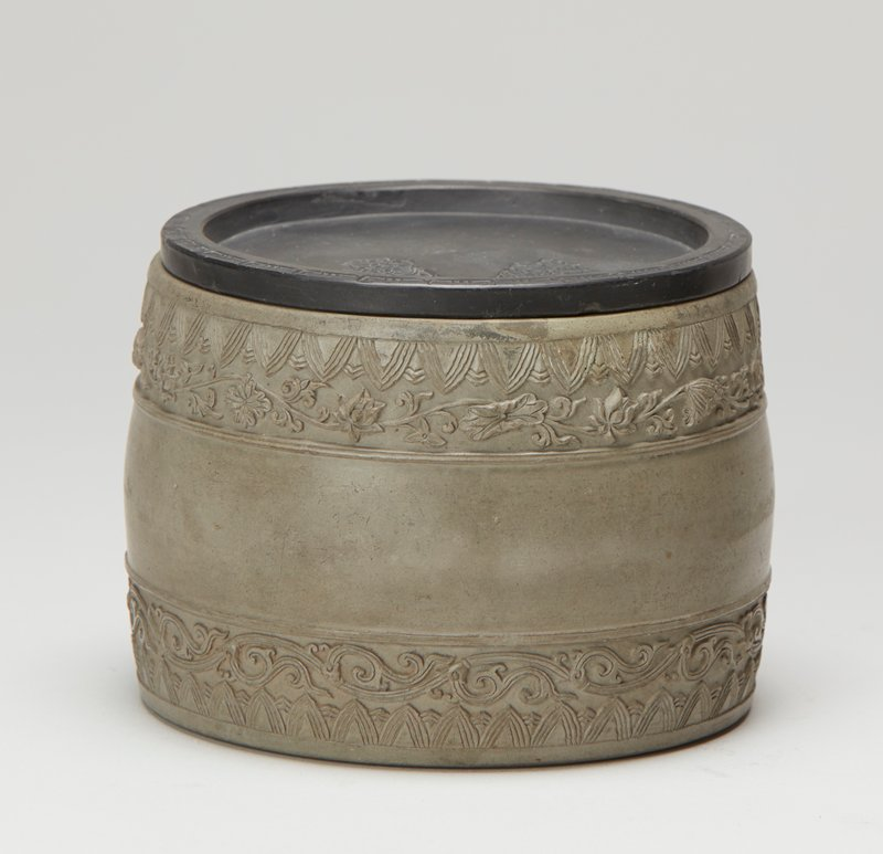 Yixing ware; lidded container with very heavy foot; grey container carved with bands around top and bottom with continuous scrolls and foliage and geometric patterns; black lid stamped with cartouche with plant forms around three sides on underside, geometric design carved into edge of lid and stamped foliage on top