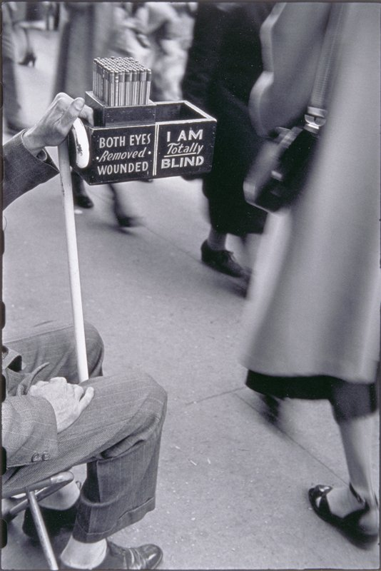 legs and hands of man visible at L; man holds a white cane in his PL hand and a box with pencils printed 'BOTH EYES Removed WOUNDED/I AM totally BLIND'; pedestrians visible at R