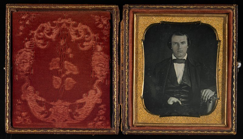 man wearing white shirt, bowtie, jacket and vest with PL hand resting on table and defective PR hand on lap; in leather case embossed with flowers on front and back and velvet with floral design and putti opposite image