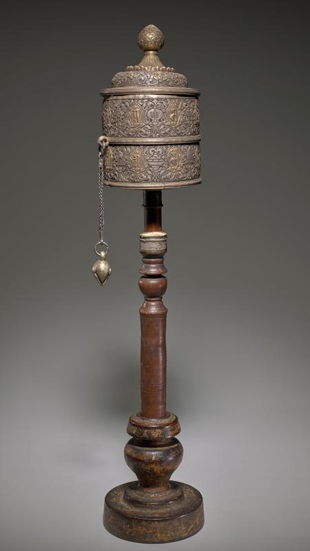 Tall, slender turned wood base resting on a wide foot; metal cylinder with repousse scrolls and inscription and domed metal lid with organic finial; chair with weight attached to one side of cylinder; cloth-covered paper roll (d) inside cylinder (should be removable, but is stuck inside)