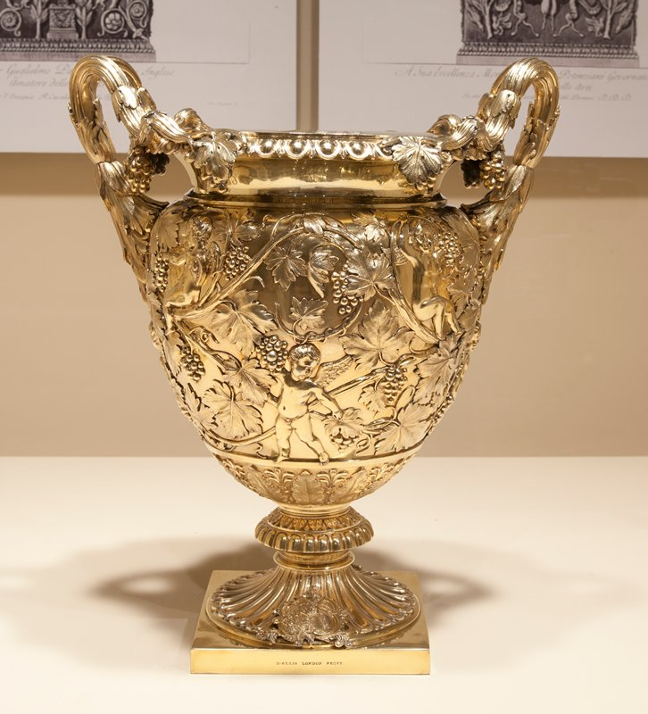 classical vase form; on square base with fluted pedestal feet; cast coat of arms; decorated with putti amidst scrolling grapevine; collars engraved on each side with two crests (dragon and lion) Description (consistent for each cooler): Classical vase form; on square base with fluted pedestal feet; cast coat of arms; decorated with putti amidst scrolling grapevine; collars engraved on each side with two crests (dragon and lion). Coat of arms: those of Sawbridge-Erle-Drax with Grosvenoer in pretence, probably for Johan Samuel Wanley Sawbridge of Olantigh Towers, Kent, Holnest House, Co. Dorset, and Ellerton Abbey, Co. York (1800-1887). He married in 1827 Jane Frances, sister and sole heiress of her brother Richerd Erle-Drax-Grosvenor, M.P., of Charlborough Park, Dorset (dd. 1828). By 1853, Burke's Visitations of Seats and Arms, vol. 2, records this latter house as the seat of John Samuel Wanley Erle-Drax, M.P., Captain of the East Kent Militia. Stamps/Inscriptions/Stickers: 1a-c) - D. ELLIS LONDON FECIT - stamped, on front of base; - SH2097 - incised on bottom of base; - A501/091 - in black, on bottom of base; - EEBJW - and three stamps near top of liner; - 2 - etched three times on bottom of removable liner. 2a-c) - D.ELLIS LONDON FECIT - stamped, on front of base; - SH2097 - incised on bottom of base; - A501/ - and illegible numbers in black, on bottom of base; - EEBJW - and three stamps near top of liner and side of collar; - A501/692 - in black, on bottom of removable liner. 3a-c) - D.ELLIS LONDON FECIT - stamped, on front of base; - SH2097 - incised on bottom of base; - A501/693 - in black, on bottom of base, bottom of liner and bottom of collar; - M209810 1(4) - on sticker on bottom of base; - EEBJW - and three stamps near top of liner and side of collar. 4a-c) - D.ELLIS LONDON FECIT - stamped, on front of base; - SH2097 - incised on bottom of base; - M209810 1(4) - sticker on bottom of base; - A501/691 - in black, on bottom of base, liner and collar; - EEBJW - and three stamps near top